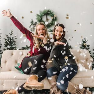 two women on couch in photography studio throwing confetti