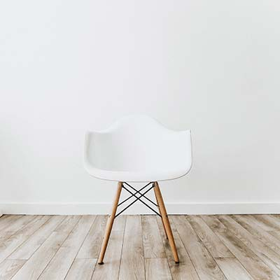 white eames style chair on white wall and wood floor